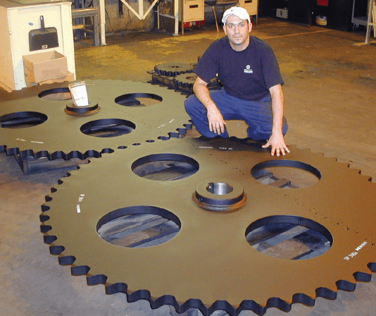 Man standing with Tsubaki sprocket to test for quality