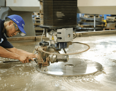 Man using a waterjet machine to custom manufacture a sprocket